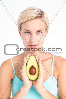 Attractive woman showing half of an avocado