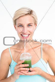 Attractive blonde drinking green juice