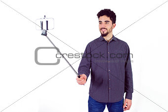 Casual man using a selfie stick
