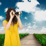 Composite image of casual young woman using binoculars