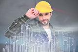 Composite image of smiling handyman holding helmet