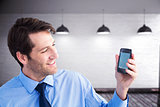 Composite image of smiling businessman showing smartphone to camera