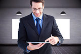 Composite image of businessman standing while using a tablet pc