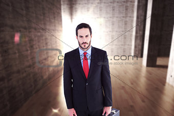 Composite image of serious handsome businessman holding briefcase