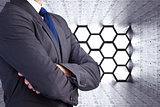 Composite image of man in a suit with folded arms