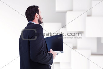 Composite image of businessman in suit holding laptop