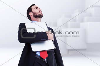 Composite image of concentrating businessman in suit holding laptop