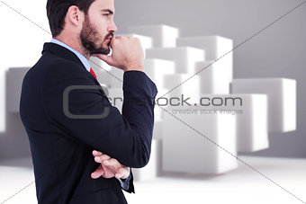 Composite image of thinking businessman standing with hand on chin