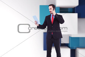 Composite image of businessman talking on phone holding tablet pc