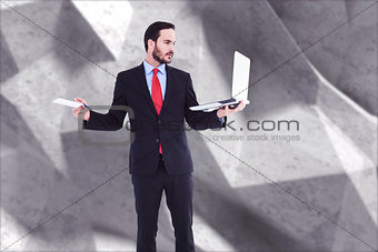 Composite image of handsome businessman holding his laptop