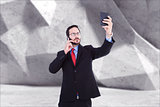 Composite image of businessman holding calculator while talking on phone