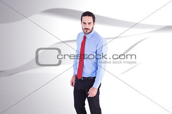 Composite image of serious businessman in suit standing