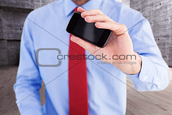 Composite image of hand of businessman showing smartphone