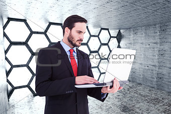 Composite image of focused businessman using his laptop