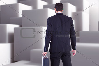 Composite image of rear view of businessman holding a briefcase