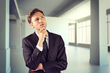 Composite image of young businessman thinking with hand on chin