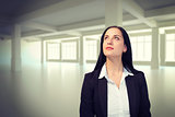 Composite image of pretty businesswoman looking up