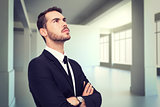 Composite image of thinking businessman with his arms crossed