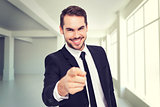 Composite image of happy businessman pointing at camera