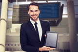 Composite image of smiling businessman showing his tablet pc
