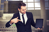 Composite image of happy businessman pointing with his tablet