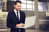 Composite image of smiling businessman standing and using laptop