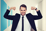 Composite image of happy businessman in suit cheering