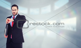 Composite image of frowning young businessman checking time