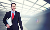 Composite image of handsome businessman holding briefcase and laptop