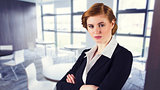 Composite image of stylish redhead businesswoman in suit