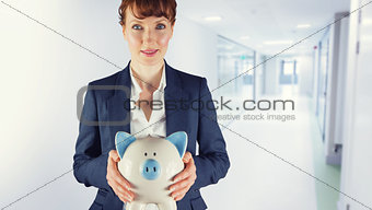 Composite image of businesswoman showing piggy bank