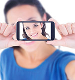 Composite image of pretty brunette taking a selfie
