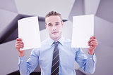 Composite image of businessman holding pages