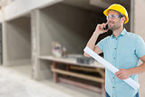 Composite image of male architect with blueprint talking on mobile phone