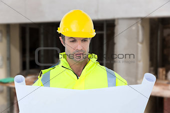 Composite image of architect analyzing blueprint