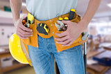 Composite image of technician with tool belt around waist