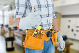 Composite image of technician with tool belt around waist holding pliers