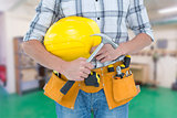 Composite image of technician holding hammer and hard hat