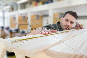 Composite image of worker measuring wooden plank