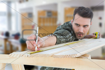 Composite image of worker marking on wooden plank