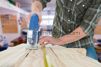 Composite image of carpenter cutting wooden plank with electric saw
