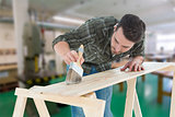 Composite image of worker using brush on wooden plank