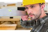 Composite image of carpenter using spirit level