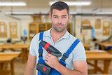 Composite image of portrait of confident carpenter holding power drill