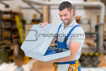 Composite image of happy repairman opening toolbox