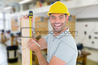Composite image of construction worker using measure tape to mark on plank