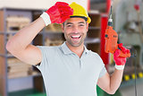 Composite image of smiling manual worker holding drill machine