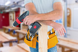Composite image of midsection of male carpenter with power drill and plank