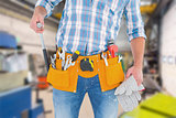 Composite image of midsection of handyman holding hammer and gloves
