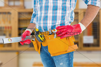 Composite image of midsection of handyman holding spirit level